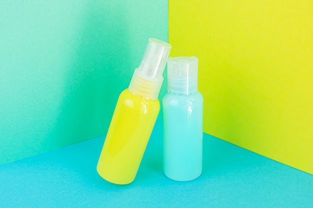 Flaconi per la cosmetica gialli e blu sullo stesso spazio colorato. elegante concetto di essenze biologiche, prodotti di bellezza e salute. copia spazio, minimalismo, effetto levitazione.