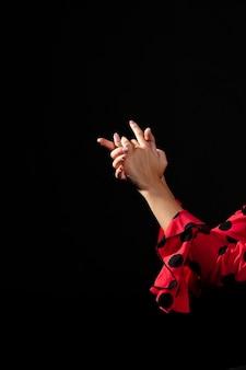 Flamenca del primo piano che si tiene per mano sul fondo nero