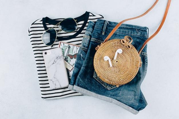 Flat lay con abbigliamento e accessori femminili. t-shirt a righe, pantaloncini, borsa in rattan alla moda.