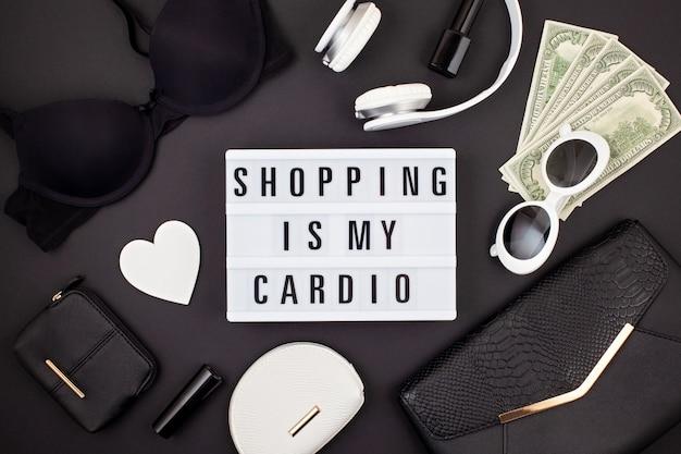 Flat lay con lightbox e citazione divertente lo shopping è il mio cardio