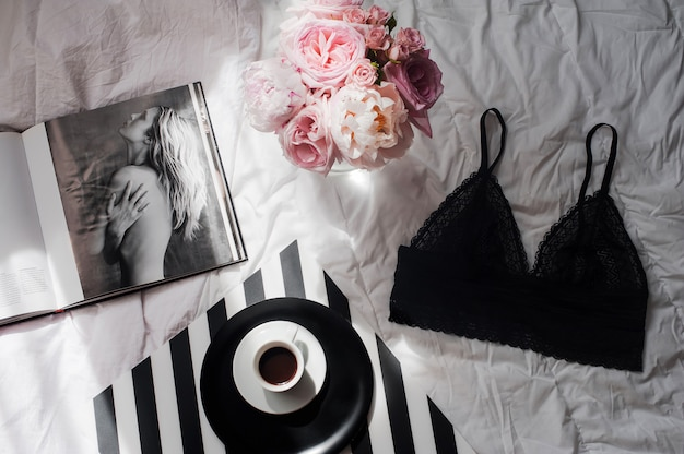 Flat lay con lingerie di pizzo, bouquet di rose, caffè e rivista