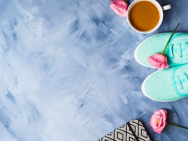 Flat lay con scarpe, caffè e fiori