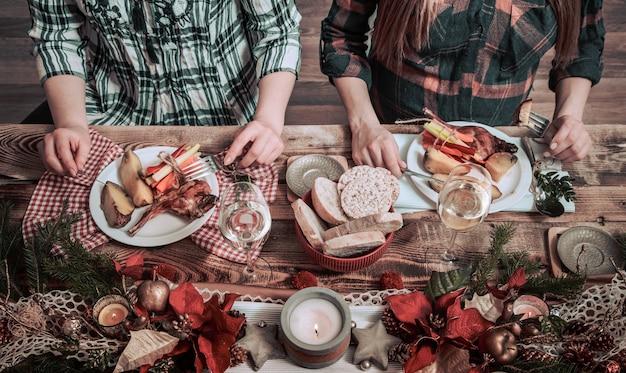 Flat-lay di mani di amici che mangiano e bevono insieme. vista dall'alto di persone che hanno festa, si riuniscono, celebrano insieme al tavolo rustico in legno con diversi snack di vino e fingerfood