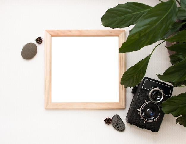 Flat lay mock up, vista dall'alto, cornice in legno, vecchia macchina fotografica, pianta e pietre.