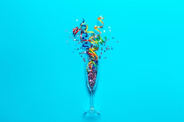 Flat lay of celebration. bicchiere di champagne con stelle filanti colorate
