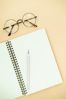 Flat lay vista dall'alto foto di matita, occhiali e blocco note