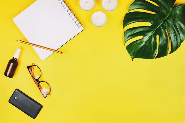 Flatlay aziendale con cellulare, occhiali, foglia di filodendro e altri accessori. sfondo giallo.