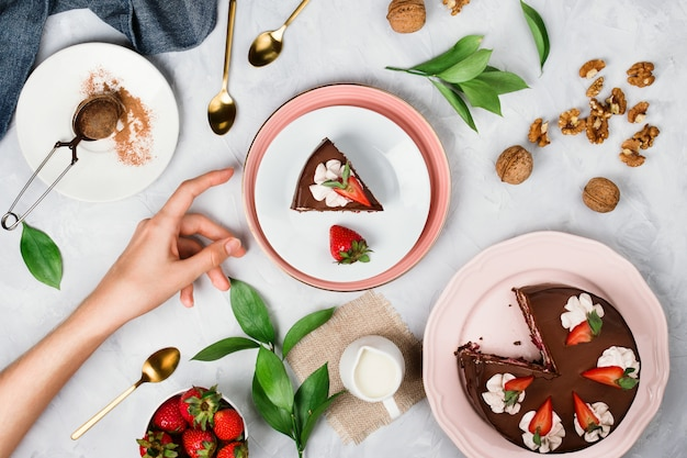 Flatlay con la mano della donna che raggiunge per un pezzo di torta vegana al cioccolato circondata da noci, fragole, cacao in polvere e altri ingredienti da dessert su sfondo di cemento