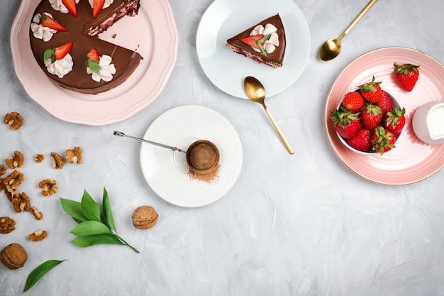 Flatlay con torta al cioccolato vegana, fragole, noci, cacao e altri ingredienti da dessert su sfondo di cemento con copyspace