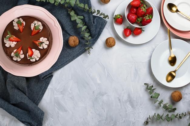 Flatlay con torta al cioccolato vegana, fragole, noci e altri ingredienti da dessert su sfondo di cemento con copyspace