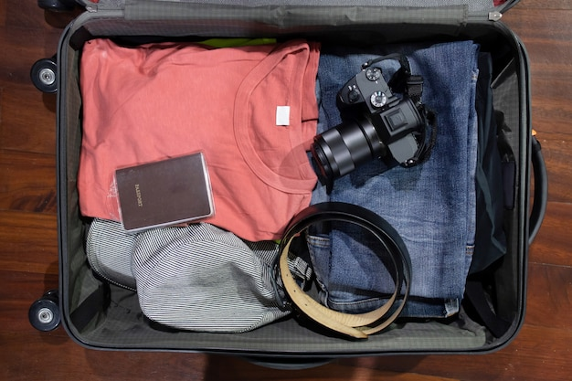 Flatlay della macchina fotografica di withclothes della valigia di viaggio aperto e passaporto sui precedenti di legno