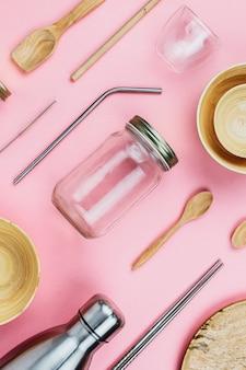 Flatlay di vari utensili e stoviglie da cucina sostenibili a spreco zero: bottiglie di vetro e metallo, ciotole di bambù in legno, cannucce ecologiche ecc. sul rosa