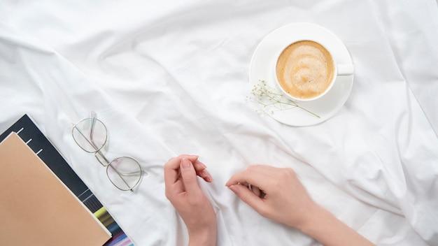 Flatlay mattutino nel letto bianco. caffè e routine mattutina. leggere a letto.