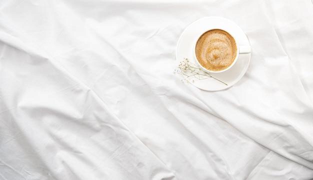 Flatlay mattutino nel letto bianco. caffè e routine mattutina.