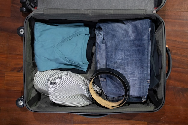 Flatlay of open travel suitcase with clothes on the wooden background