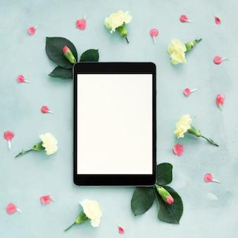 Flay laici la tavoletta digitale copia spazio circondato da fiori di garofano