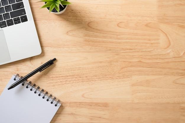 Flay lay, scrivania da tavolo vista dall'alto con computer portatile, tastiera, blocco note, penna e pianta verde