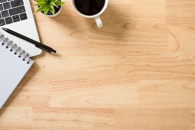 Flay lay, scrivania da tavolo vista dall'alto con laptop, tastiera, caffè, penna e pianta verde
