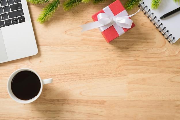 Flay lay, scrivania da tavolo vista dall'alto con laptop, tastiera, caffè, penna, foglie di pino e regalo rosso