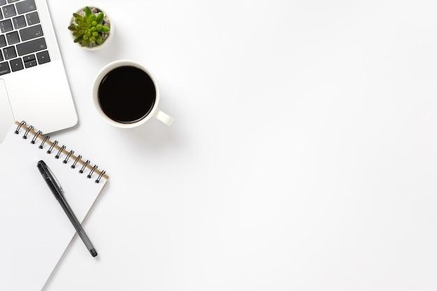 Flay lay, scrivania da tavolo vista dall'alto con tastiera, caffè, matita, foglie con spazio di copia.