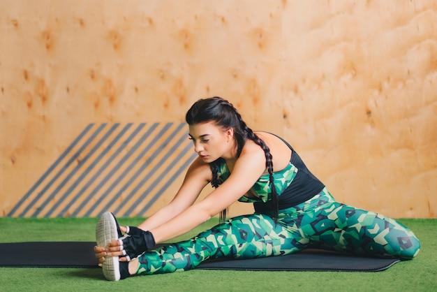 Flessibile giovane donna che si estende la gamba destra in palestra. uno stile di vita sano.