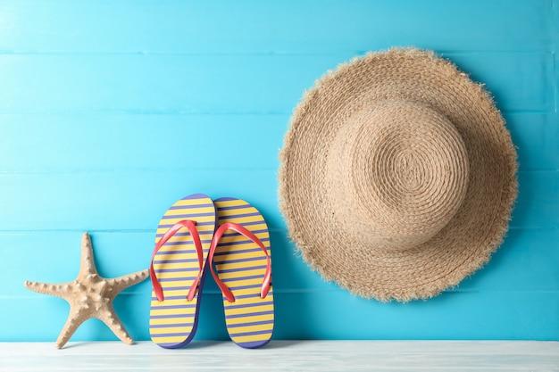 Flip-flop, cappello di paglia e stelle marine sulla tavola bianca contro il fondo di legno di colore, spazio per testo. concetto di vacanze estive