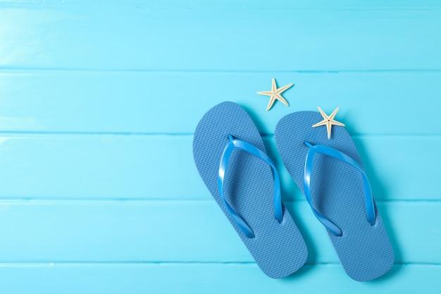 Flip-flop e stelle marine su fondo di legno di colore, spazio per testo e vista dall'alto. concetto di vacanze estive