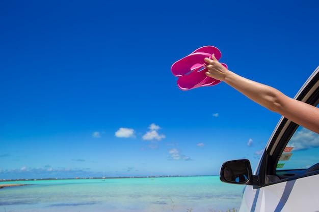 Flip flops dal finestrino di un'auto sulla spiaggia tropicale di sfondo