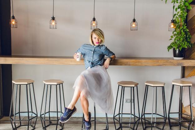 Flirty ragazza bionda con gli occhi azzurri e le labbra rosa brillante seduto in una caffetteria su una sedia a bere caffè.