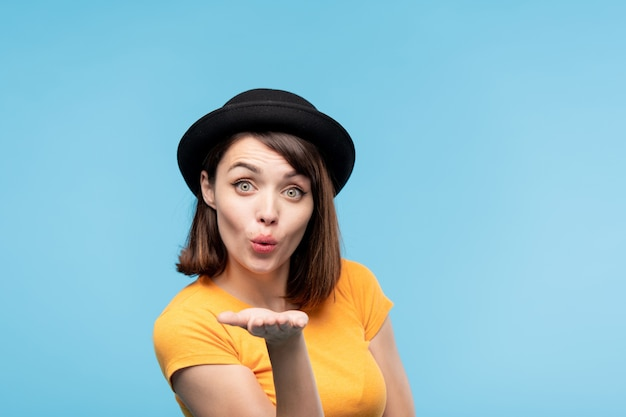 Flirty ragazza bruna con cappello nero che ti manda un bacio d'aria tenendo la mano davanti a lei in isolamento