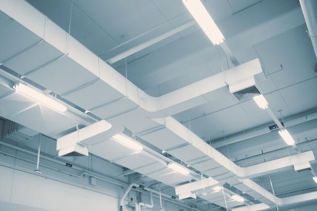 Flusso d'aria industriale in fabbrica, condotto dell'aria, pericolo e causa di polmonite nell'uomo dell'ufficio.