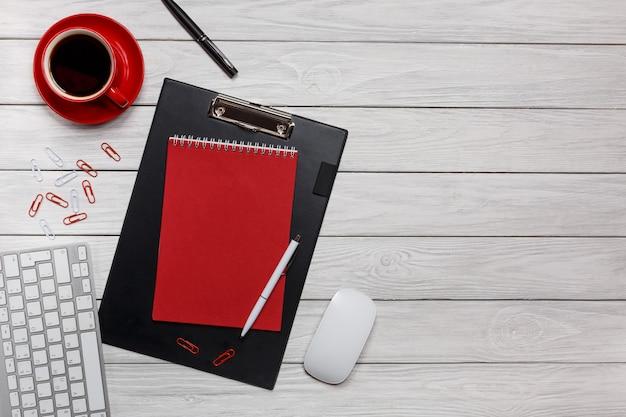 Flusso di lavoro rosso del mouse della tastiera delle graffette dell'orologio della tazza di caffè della tazza di caffè della cartella del taccuino della cartella dei bordi dello scrittorio