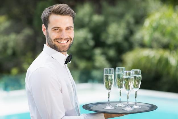 Flute di champagne di trasporto del cameriere felice sul vassoio