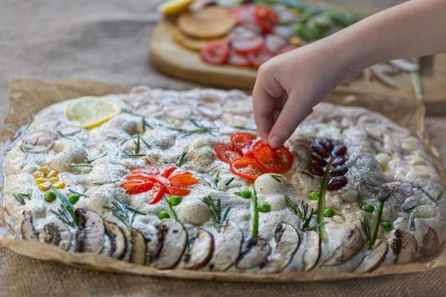 Focaccia cruda decorata in modo creativo con verdure su carta pergamena