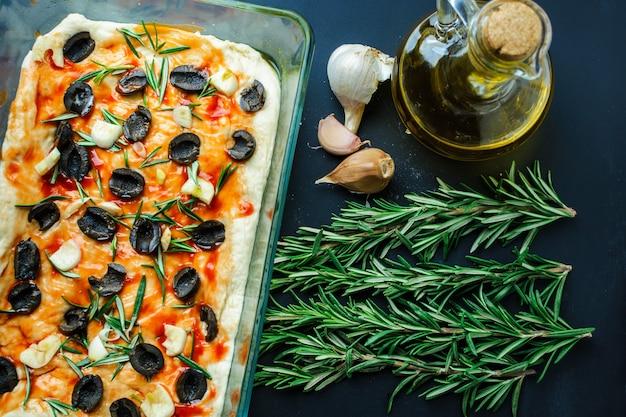 Focaccia domestica con olive e rosmarino su un tavolo nero