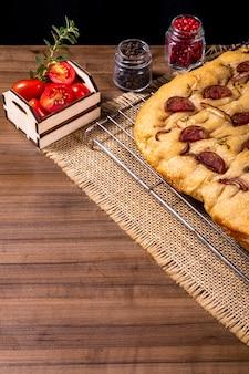 Focaccia tradizionale italiana con peperoni, pomodorini, olive nere, rosmarino e cipolla