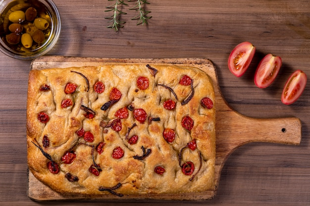 Focaccia tradizionale italiana con pomodorini, olive nere e rosmarino