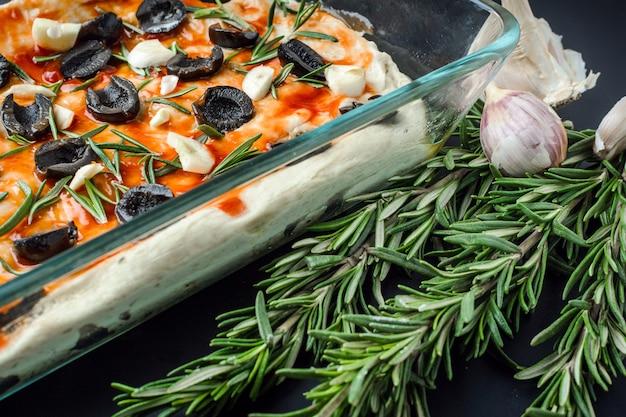 Focaccia vegetariana italiana di pane fatto in casa con olive, rosmarino e aglio
