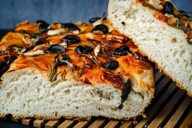 Focaccia vegetariana tradizionale italiana di pane fatto in casa con olive, rosmarino e aglio