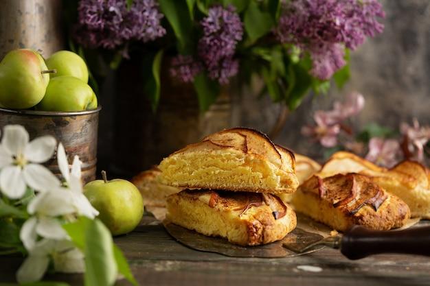 Focaccine di cannella mela fatta in casa con fiori lilla e rami fioriti di mela. colazione inglese o brunch al villaggio