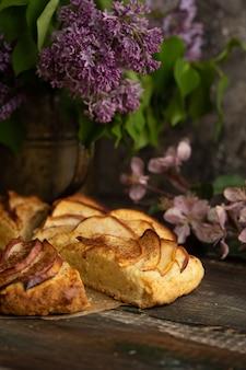 Focaccine di mele alla cannella fatte in casa con fiori lilla e rami fioriti di mela