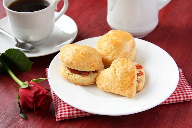 Focaccine fatte in casa con marmellata di fragole e una tazza di tè