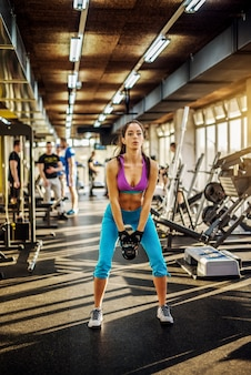 Focalizzato giovane ragazza sana fitness facendo esercizio con kettlebell davanti a lei in palestra.