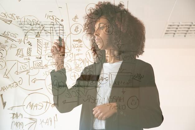 Focalizzato giovani imprenditrici scrivendo a bordo virtuale. giovane responsabile femminile afroamericano concentrato che tiene indicatore e che fa annotato sul grafico. strategia, business e concetto di gestione