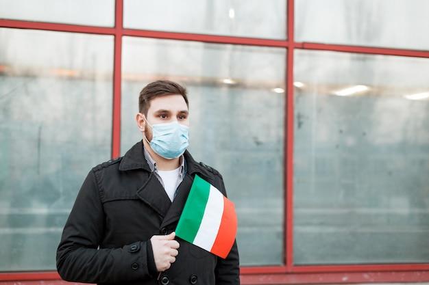 Focolaio di diffusione di coronavirus in italia. uomo in maschera medica, maschera protettiva con bandiera italiana. epidemia virale, influenza epidemia di coronavirus cinese. inquinamento atmosferico, nuovo coronavirus in europa ue.