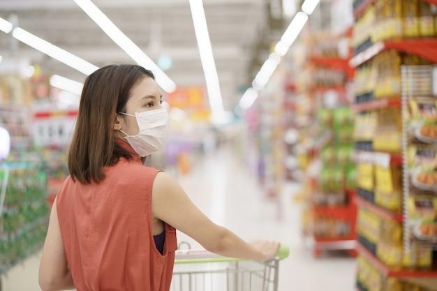 Focolaio diffondente covid-19. donna in maschera protettiva medica panico comprare cibo. paura del coronavirus.