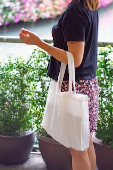 Focus di borse di stoffa bianca e donna asiatica.