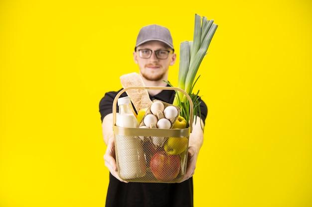 Focus sul carrello con generi alimentari su sfondo giallo, servizio di consegna di alimenti agricoli
