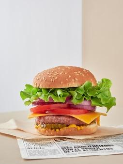 Focus sul cheeseburger in primo piano, molta lattuga fresca verde, cipolla rossa, fette di pomodoro e sottaceti