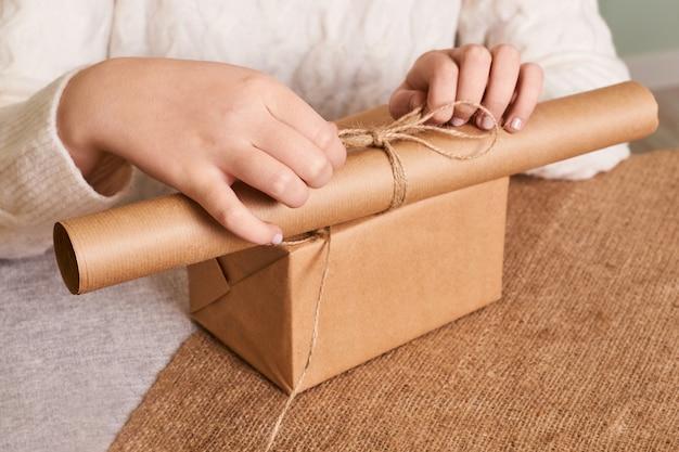 Focus sulle mani della donna in scatola da imballaggio maglione lavorato a maglia bianco. carta da regalo artigianale e spago naturale. buone vacanze, sorpresa. regali per il santo stefano